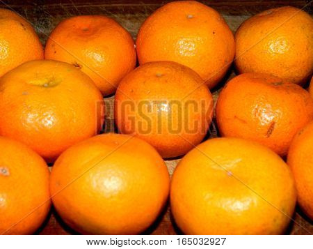 on a wooden chopping board lined with bright orange citrus tangerine on a horizontal surface in front view