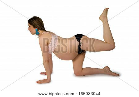 Pregnant woman is exercising her body on floor