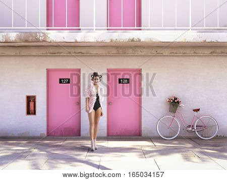woman walking from abandoned motel with pink doors.