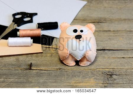 Cute stuffed teddy bear toy. Teddy bear with a heart made of felt. Handicraft materials on wooden background with copy space for text. Simple handmade toy on Valentine's day, mother's day