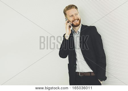Modern Redhair Man With Mobile Phone Standing In The Office