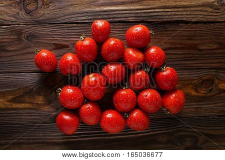 Red tomatoes with water drops. Tomatoes of different varieties. omatoes background. Fresh tomatoes Healthy food concept. Colorful festive still life. Loosely laid tomatoes in different positions.