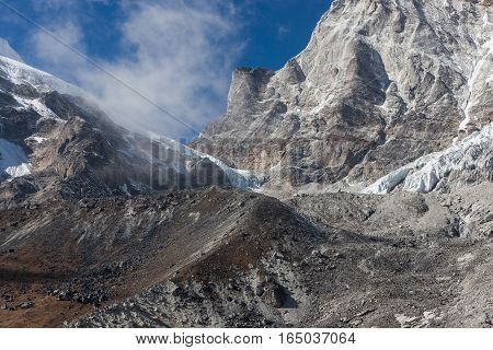 Grey Glacier Coming Down The Big Mountain Rock Covered With Snow On A Clear Day. Himalaya Mountains,