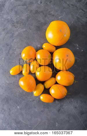 Tomatoes of different varieties. Colorful tomatoes Tomatoes background. Fresh tomatoes Healthy food concept. Colorful festive still life. Loosely laid tomatoes in different positions. Yellow tomatoes