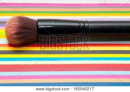 Make Up Brush On A Bright Colorful Striped Background