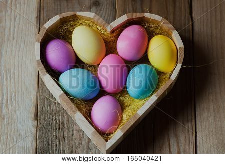 Colorful Easter eggs in a wooden heart shaped bowl