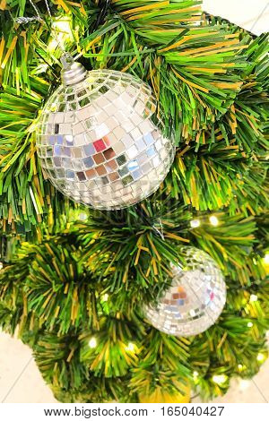 Mirror disco ball hanging on christmas tree for celebration