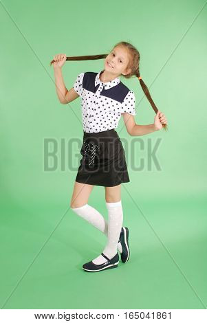 School girl plays with plaited hair. Lovely girl hold plait of hair in hands and look in the camera on green