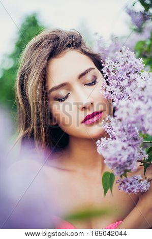 Portrait of young beautiful woman posing closed eyes among lilac flowers. Professional make-up and hairstyle. Perfect skin. Fashion photo. Natural beauty.