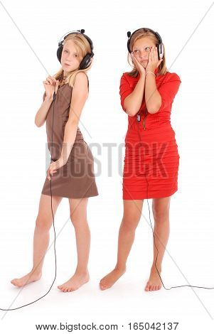 Two pretty teenage girls listening music on her headphones isolated on white background