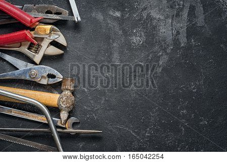 Tools: wrench adjustable wrench hacksaw screwdriver hammer hacksaw on the black cement background with copy space.