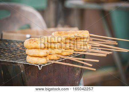 Toast sticky rice coated by egg yolk with stick on grille of strove. It's traditional snack in north part of Thailand which taste are sweet and salty.