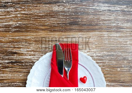 St Valentines Day place setting en white red tone. Plate cutlery line napkin decorative heart on wooden background with copy space. Love romantic dinner concept.