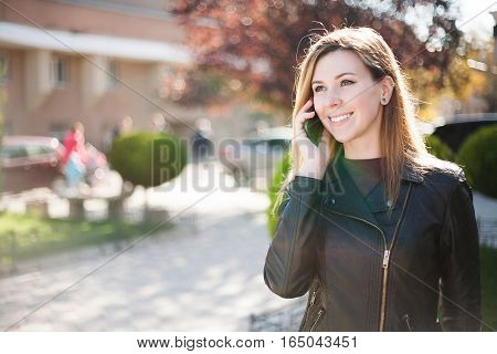 Young smiling woman talking on mobile phone. Autumn city background