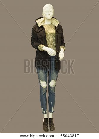 Full-length female mannequin dressed in warm brown jacket and blue jeans. No brand names or copyright objects.