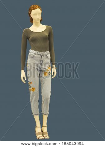Full-length female mannequin dressed in jumper and blue jeans isolated. No brand names or copyright objects.