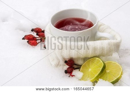 Hot red tea from rose hips and lemon outside in the snow winter drink with vitamin against flu and common cold copy space selected focus narrow depth of field