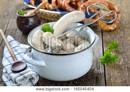 Hot Bavarian white sausages in an enamel cooking pot served on a wooden table with fresh pretzels and sweet mustard