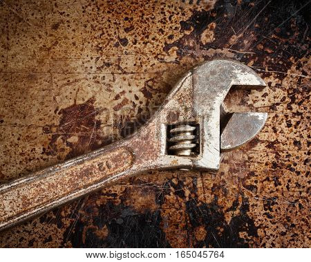 Rusted adjustable wrench on distressed and rusted metal.