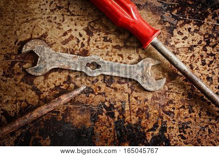 Rusted wrench and screwdrivers on distressed metal.