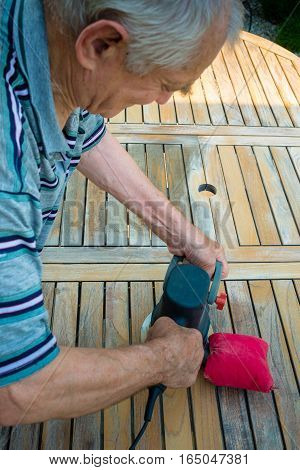 Old man - carpenter working with electric sander in the garden - polishing old color from wooden table