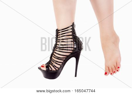 Female leg with sexy black high heels shoes for striptease and barefooted female leg with red nails are isolated on white background.