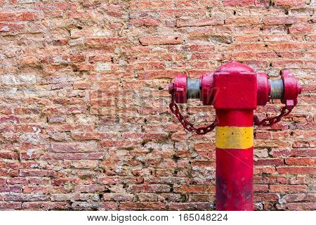 Fire Hydrant at the Weathered stained old dark brown Wall Dirty Brick Wall