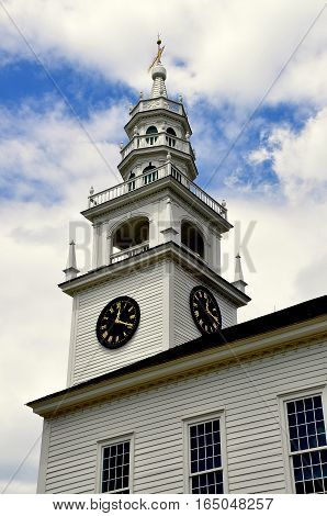 Jaffrey Center New Hampshire - July 11 2013: Tiered steeple at the 1775 Original Meeting House church with clock face oculi windows cupola and weather vane