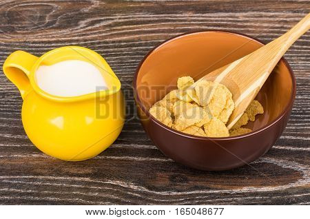 Corn Flakes In Brown Bowl And Jug Milk On Table