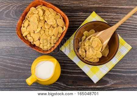 Corn Flakes In Bamboo Bowl And Jug Milk On Table
