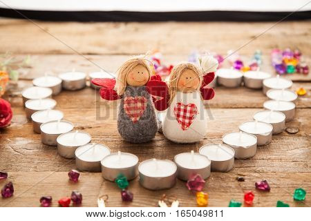 Valentine's day angels in made of candles heart with letters signed by colorful stones. Word Love signed with letters and toy couples.