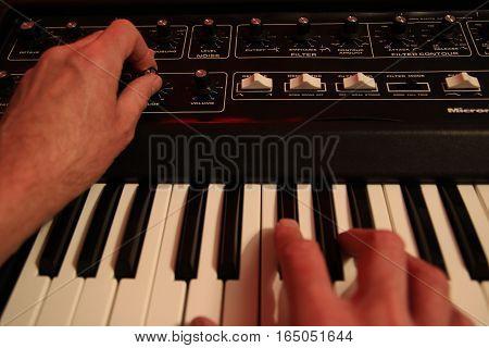 Man Adjusting And Playing Vintafge Analogue Music Synthesizer