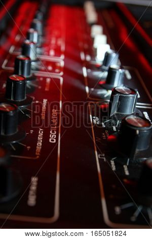 Vintage Music Synthesizer Knobs And Controls In Dramatic Lighting