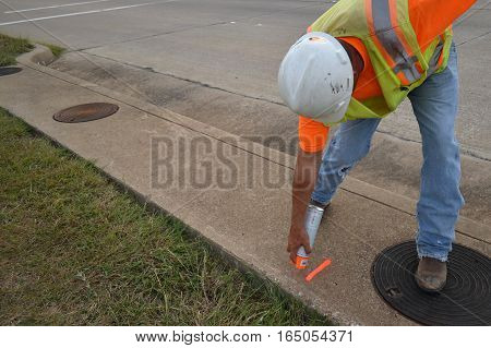 Man in safety gear spray painting numbers on a sidewalk while surveying.