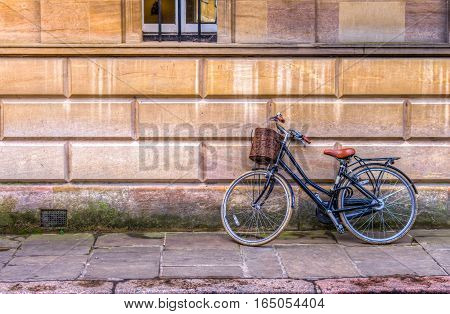 Vintage bicycle with a basket in an iconic old street of Cambridge