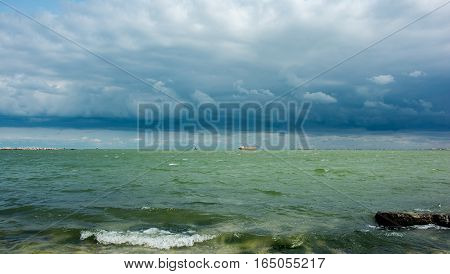 landscape with rain clouds over the sea and the ship leaving the port into the open sea