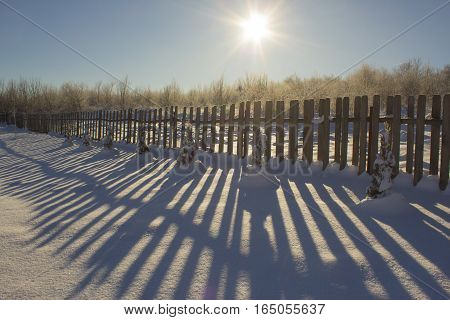 Winter Snowy Vintage Old Backyard Wooden Fence, Beautiful Shadows On Sunny Snow