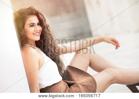 Feminine beauty. Curly hair young smiling woman model. A young, smiling and attractive woman is leaning on a white wall. Sitting on the ground. Face with makeup. She has long curly hair. Sensual and radiant beauty. Intense emotions.