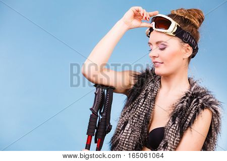 Woman Holding Ski Goggles And Poles