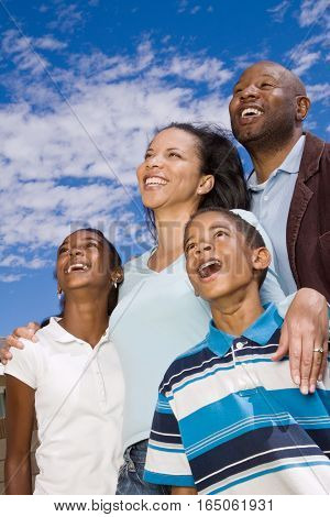 Happy African American family standing outside smiling.