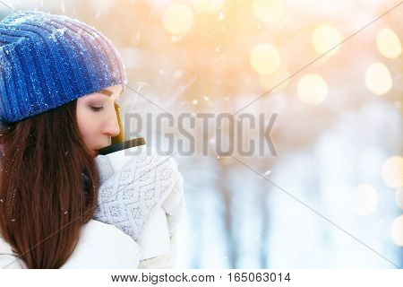 Girl enjoys the snow falls. Young woman drinking tea in the forest during a snowfall. Enjoying nature, wintertime.