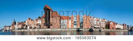 Gdansk old city in Poland. Wide panorama with the oldest medieval port crane (Zuraw) in Europe and the quay along the riverbank of Motlawa River.