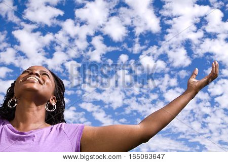 Woman with open arms with clouds in the background.p