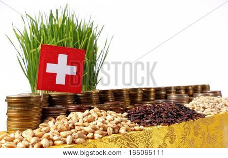 Switzerland Flag Waving With Stack Of Money Coins And Piles Of Wheat And Rice Seeds