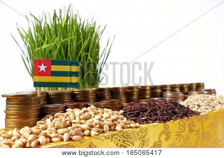 Togo Flag Waving With Stack Of Money Coins And Piles Of Wheat And Rice Seeds