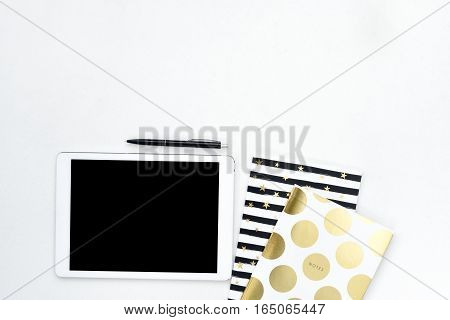 Flat lay photo of office white desk with tablet and gold notebook with copy space background. Mock up template.