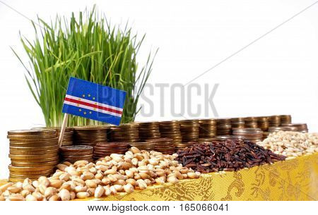 Cape Verde Flag Waving With Stack Of Money Coins And Piles Of Wheat And Rice Seeds
