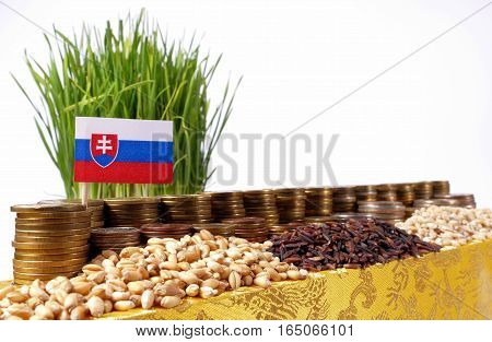 Slovakia Flag Waving With Stack Of Money Coins And Piles Of Wheat And Rice Seeds