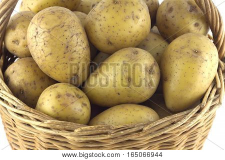 Ripe potatoes in brown wicker basket isolated on white closeup