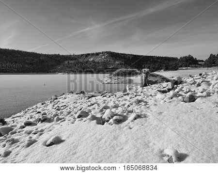 Fresh snow covers the frozen over Ochoco Reservoir and its rocky shores in Crook County in Central Oregon on a sunny winter day.